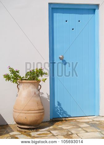 A Typically Blue doorway with an adjacent Terracotta plant pot , Corfu, Greece