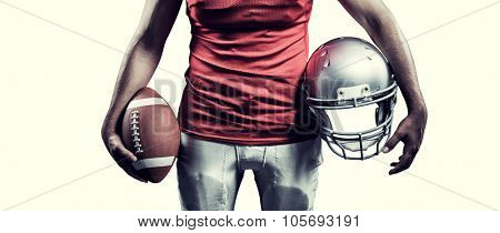 Mid section of sportsman holding American football and helmet against white background with vignette