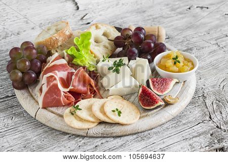 crackers, figs, nuts, jam, served on a light wooden board
