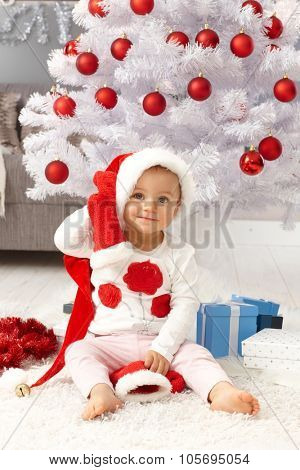 Happy little girl sitting by christmas tree in santa hat, smiling.