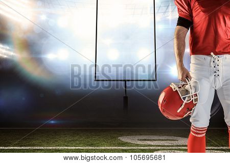 Front view of American football player holding his helmet against american football arena