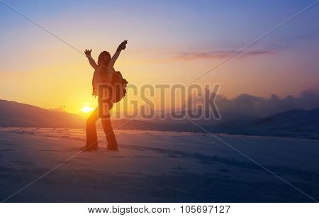 Happy joyful woman having fun outdoors, standing on the mountains with raised up hands on the mountain covered with snow, active winter holidays