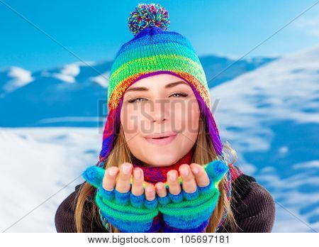 Portrait of happy joyful woman wearing colorful knitted hat and gloves with pleasure sending an air kiss, having fun on winter holidays in the mountains covered with snow