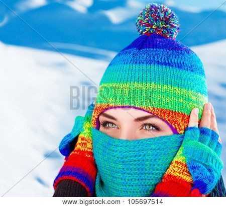 Closeup portrait of cute female wearing stylish colorful hat and covering half of face with scarf, spending time outdoors in cold winter day