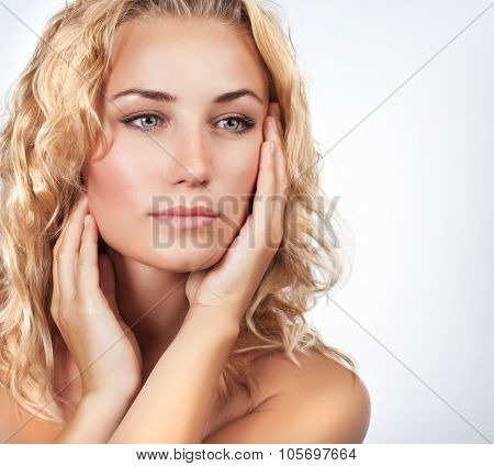 Portrait of beautiful gentle blond woman over light background, using natural cosmetics in spa salon, beauty treatment