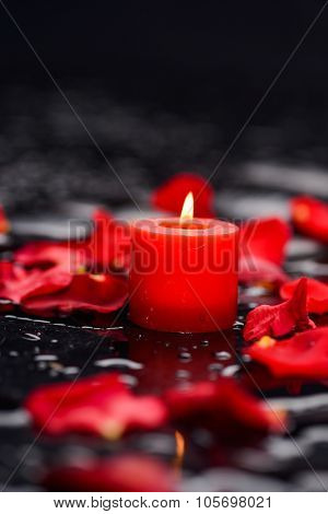 Red rose petals with candle and therapy stones