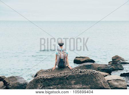 Traveler Girl Resting On Stone Coast