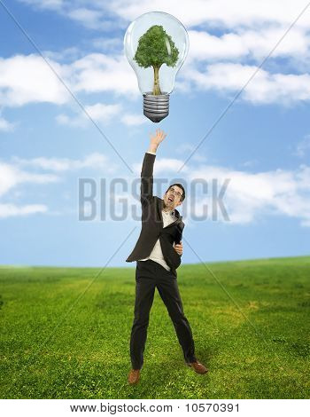 Businessman reaching green energy symbol