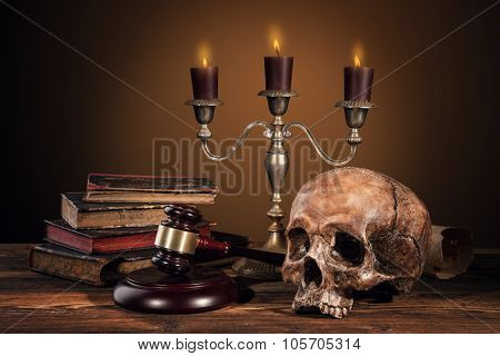 Still life art photography on human skull skeleton with blank scroll and books. Concept of judge verdict