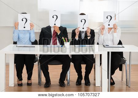 Businesspeople Hiding Face With Question Mark Sign