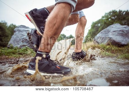 Men walking in muddy puddles in the countryside
