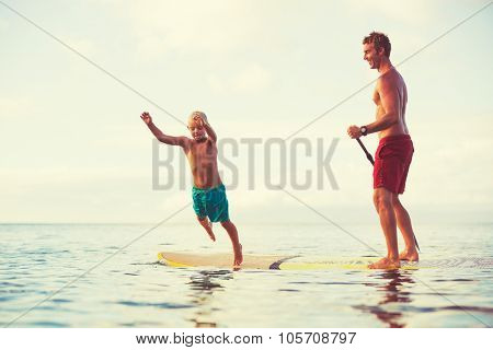 Father and son stand up paddling at sunrise, Summer fun outdoor lifestyle