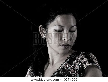 Asian Woman Looking Down On Black Background