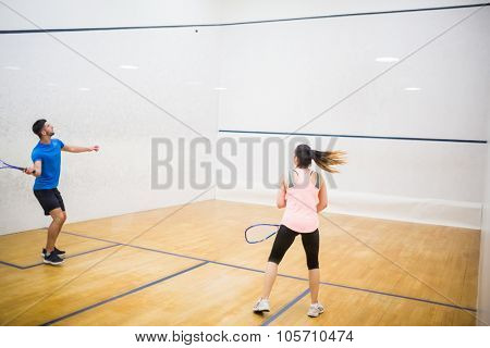 Competitive couple playing squash in the squash court