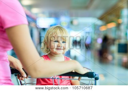 mother and cute little daughter on luggage cart in the airport