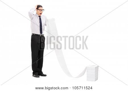 Full length portrait of an upset young businessman reading a long list stacked in front of him isolated on white background