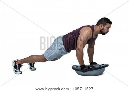 Muscular man doing bosu push ups against white background