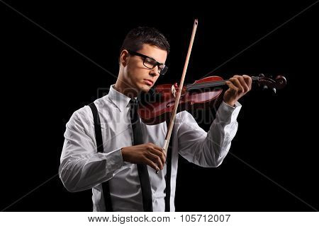 Young male violinist playing an acoustic violin on a black background