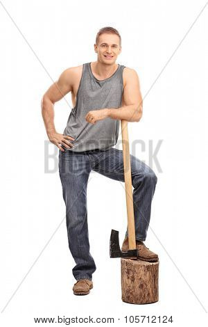 Full length portrait of a muscular young man leaning over an axe and looking at the camera isolated on white background