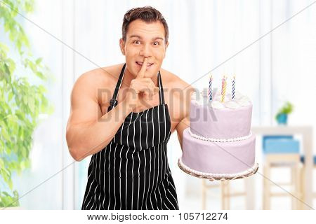 Naked pastry chef wearing only an apron holding a birthday cake and gesturing silence with his finger on his lips at home