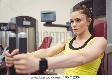 Fit woman using weights machine at the gym