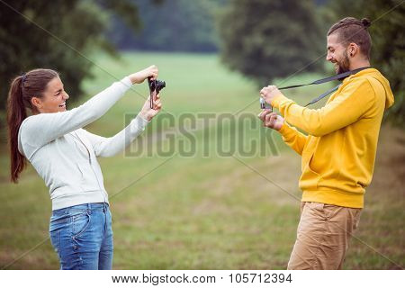 Happy couple taking photos of each other in the countryside