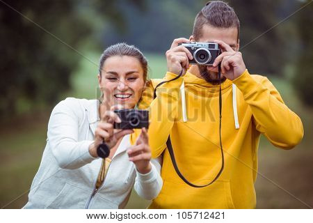 Happy couple taking photos to camera in the countryside