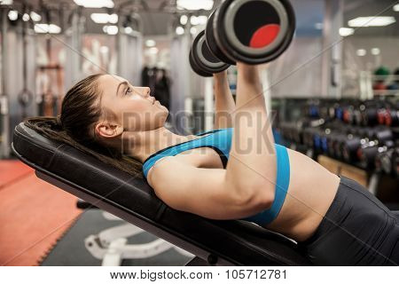 Smiling woman lifting dumbbells while lying down at the gym