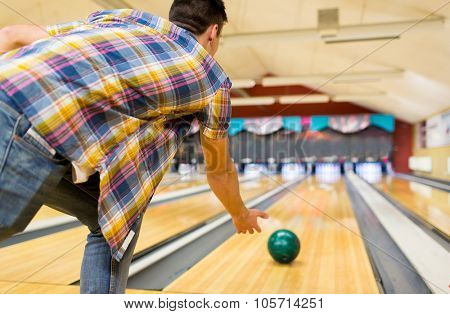 people, leisure, sport and entertainment concept - close up of young man throwing ball to alley in bowling club