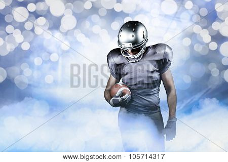 American football player looking down while holding ball against glowing background