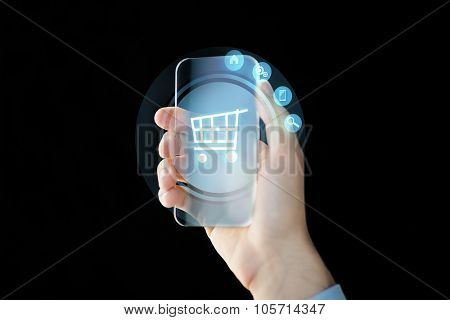 business, future technology and people concept - close up of male hand holding and showing transparent smartphone with shopping trolley icon on screen over black background