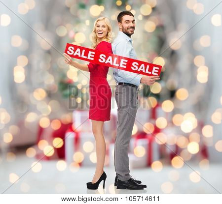 people, sale, discount and holidays concept - happy couple with red sale sign standing back to back over christmas tree lights and presents background