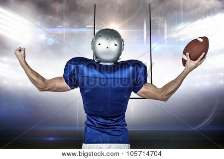 American football player flexing muscles while holding ball against american football arena
