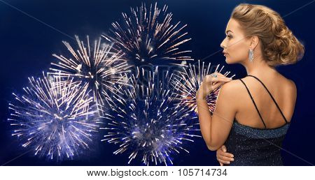 people, holidays, party, jewelry and glamour concept - beautiful woman with diamond earring over firework lights on dark blue sky  background