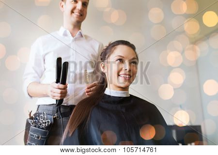 beauty, hairstyle and people concept - happy young woman with hairdresser curling hair and making hairdo at salon over holidays lights