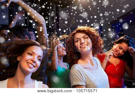 party, holidays, celebration, nightlife and people concept - smiling friends dancing at concert in club and snow effect