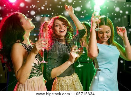 new year party, holidays, celebration, nightlife and people concept - smiling friends with glasses of non-alcoholic champagne dancing in club and snow effect
