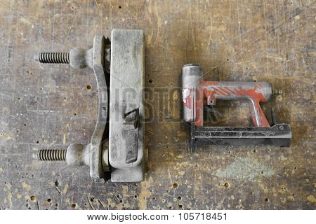 Old Used Wooden Planer And Red Air Nailer Or Nail Gun Carpenter Tools