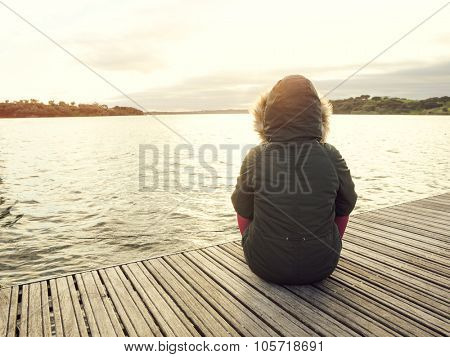 Back view of a woman sitting close to a lake