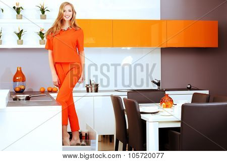 Cheerful young woman demonstrates the high quality of the kitchen furniture. Home interior.
