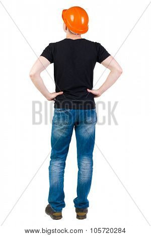 Backview of an engineer in construction helmet stands. Standing young guy. Rear view people collection.  backside view of person.  Isolated over white background. Engineer standing with hands on hips.