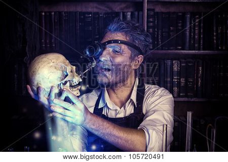 Close-up portrait of an old medieval scientist holding a skull. Alchemist. Halloween.