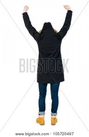 Back view of Beautiful woman in parka looking at wall and Holds  hand up.  young blonde girl standing. Rear view people. Isolated over white background.