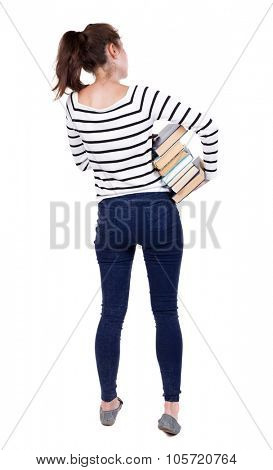 A girl carries a heavy pile of books. back view. Rear view people collection.  backside view of person.  Isolated over white background. Frenchwoman in vest is holding a stack of books under his arm.
