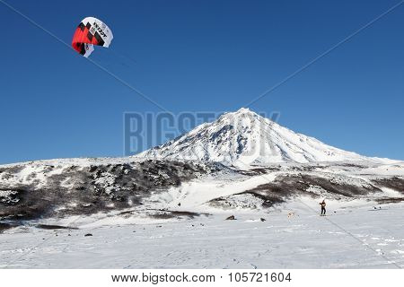 Snowkiting: Sportsman Glides On Skis On Background Volcano
