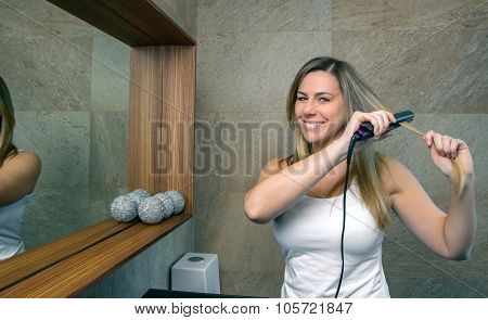 Happy young woman straightening hair with a straightener