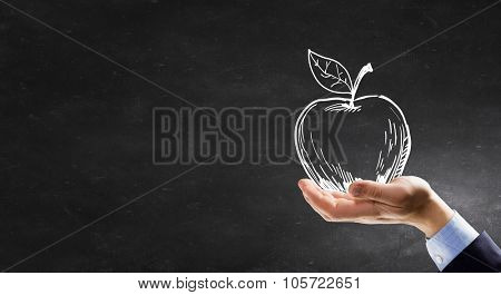 Human hand holding apple drawn symbol in palm