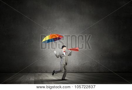 Young businessman with colorful umbrella screaming emotionally in paper trumpet