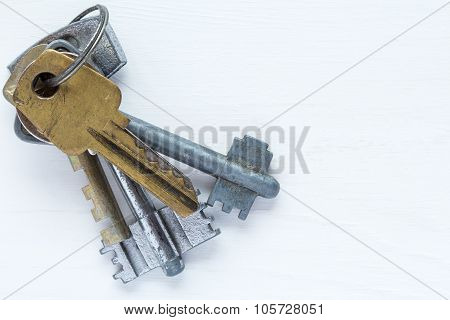 Old Keys On White Wooden Bakground