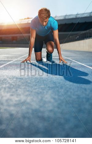 Professional Male Track Athlete In Starting Blocks